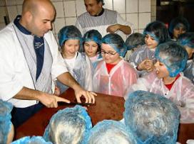 Slager leert kinderen worst maken